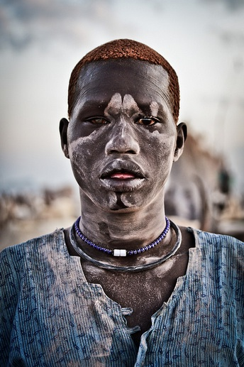A Mundari Male with orange hair which has been bleached in the sun by washing it in cow urine (Photo by Tom Mcshane) - a visual output of facial identifier, ie. hair colour/style